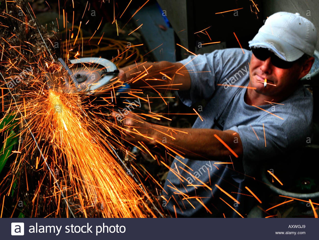 a-worker-uses-a-grinder-with-sparks-flying-off-it-AXWGJ9.jpg